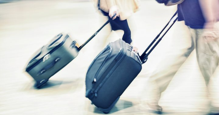 Couple walking with suitcases having asked can you take a razor in hand luggage?